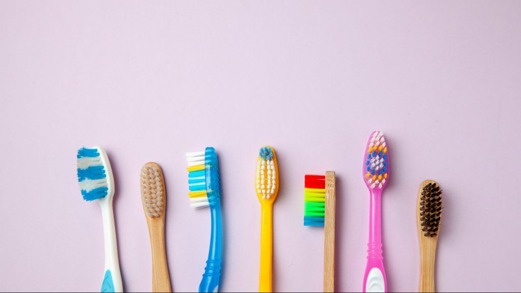 Many Colored Toothbrushes On Purple Background. How To Choose Toothbrush