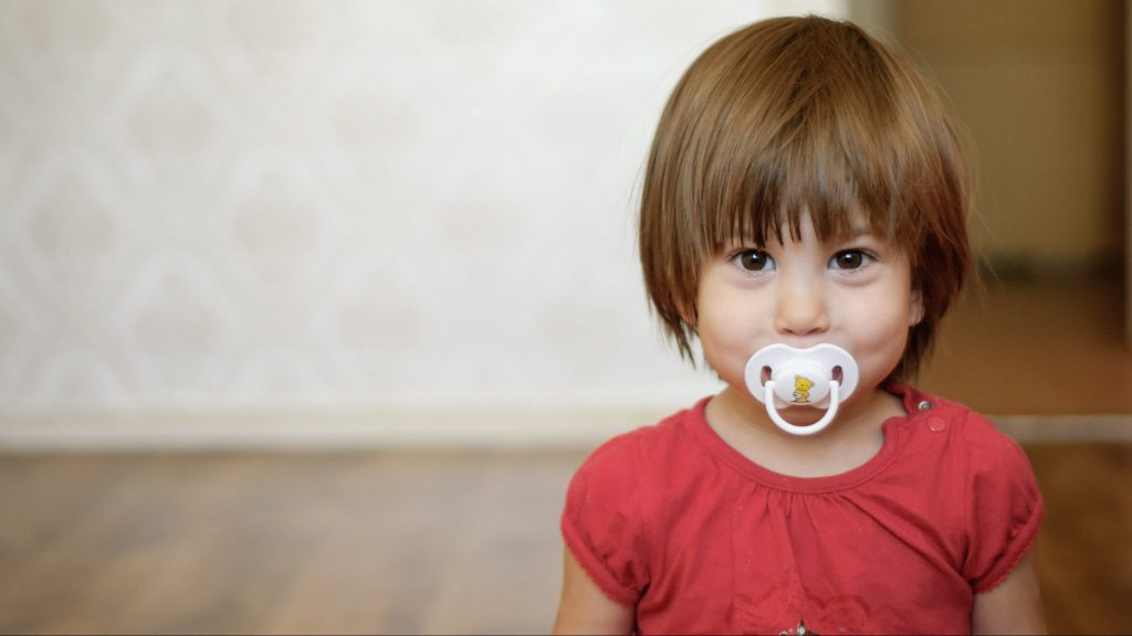 young girl with pacifier in mouth